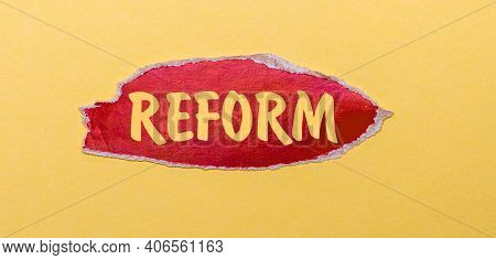 On A Yellow Background, A Sheet Of Red Paper With The Word Reform