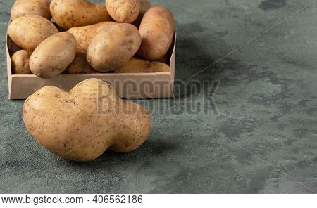 One Big Abnormal Potato On The Background Of A Ordinary Potatoes. Funny Potatoes On A Dark Green Bac