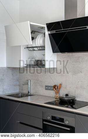 Vertical View Of Modern Kitchen With Marble Countertop, Sink, Built In Oven, Stove And Cooker Hood A