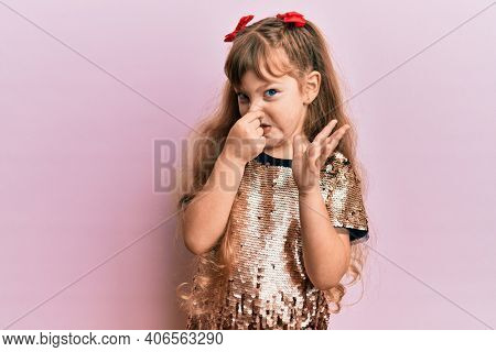 Little caucasian girl kid wearing festive sequins dress smelling something stinky and disgusting, intolerable smell, holding breath with fingers on nose. bad smell