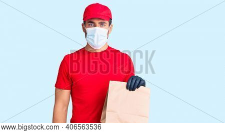 Young hispanic man delivering food wearing covid-19 safety mask holding paper bag thinking attitude and sober expression looking self confident