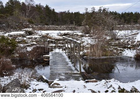 Snowy Landscape With A Wooden Footbridge Crossing A Small Creek