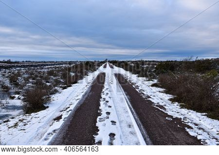 Straight Country Road Across A Wide Barren Landscape In Winter Season