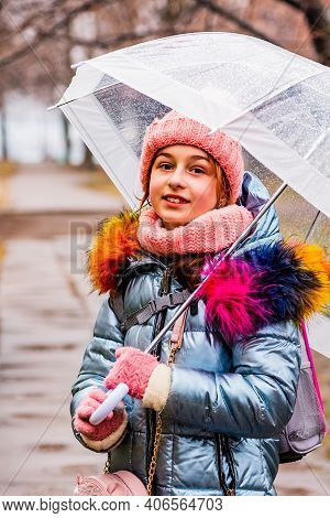 Blonde Girl In A Jacket With A Transparent Umbrella In The Rain Outside In The Cold.girl In A Jacket