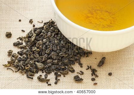 gunpowder green tea - a white cup of drink and loose leaves on canvas