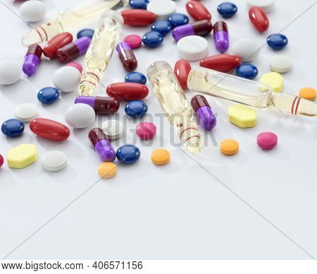 Close Up View Of The Ampule With Medicine And Pills On White Back