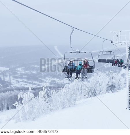 Perm Krai, Russia - January 02, 2021: Skiers Taking A Chair Lift In A Hilly Winter Landscape
