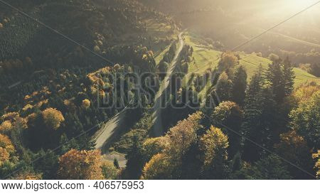 Autumn Sunset Mountain Forest Landscape Aerial View. Multicolored Hill Tree Wood Highland Nature Scenery Overview. Curved Country Road Vacation Holiday