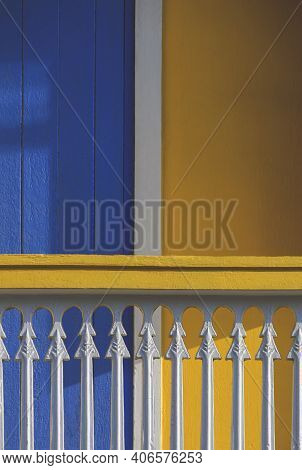 Sunlight And Shadow On Surface Of White Balustrade On Terrace In Front Of Blue Wooden Door And Yello