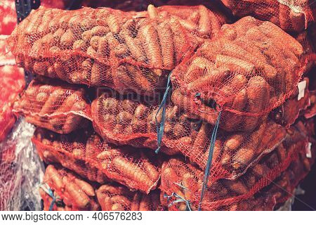 Carrot Bags Are Packed And Put Up For Sale In The Market. Bags With Carrot. Carrots In Bags Close-up
