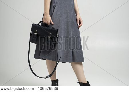 Small Black Leather Bag In A Womans Hand On A White Background. Shoulder Handbag. Woman In A White S