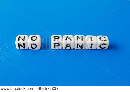No Panic Word Laid Out From White Cubes On A Blue Background. Don't Panic