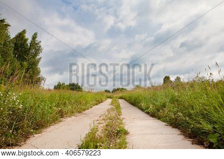 Old Concrete Road. Summer Landscape With An Abandoned Road. A Deserted Place On A Sunny Day. Everyth