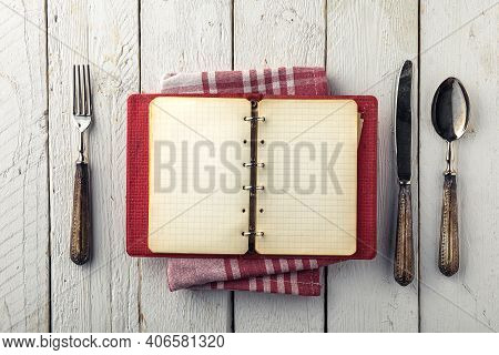 Vintage Empty Cookbook On Wooden Table With Old Silverware