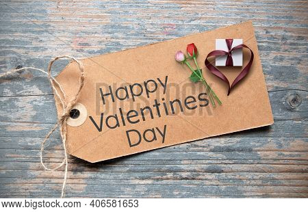 Happy Valentines Day Greeting Written On A Card With Two Roses Gift Box Wrapped In Heart Shape Ribbo