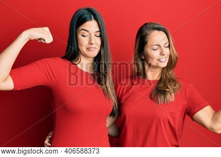 Hispanic family of mother and daughter wearing casual clothes over red background showing arms muscles smiling proud. fitness concept.