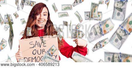 Young beautiful woman holding save our democracy protest banner smiling happy pointing with hand and finger