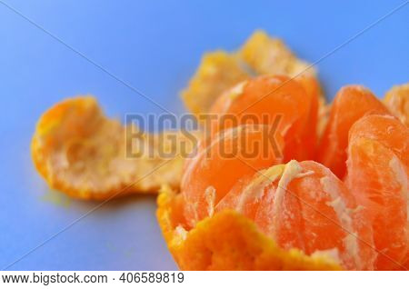 One Fresh Peeled Tangerine In An Open Peel On A Blue Table Close-up