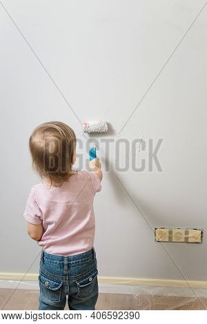 Little Child Painting The Wall With Roller In The Empty Room, Grey Background. Interior Decoration,
