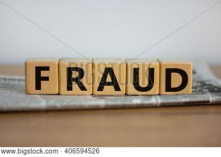 Fraud Symbol. Wooden Cubes Placed On A Newspaper. The Word 'fraud'. Beautiful Wooden Table. White Ba