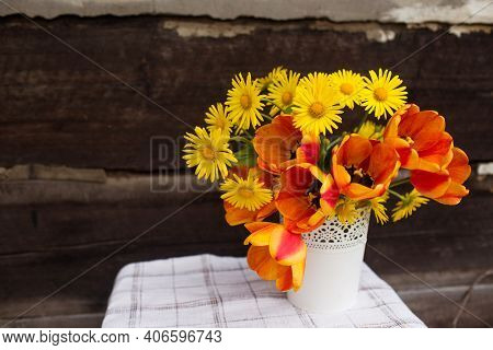 A Bouquet Of Spring Flowers In A White Vase On A Blurry Wooden Background.