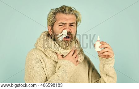Man In Scarf Hold Nasal Spray And Tissue. Cold Flu Remedies. Runny Nose And Other Symptoms Of Cold.