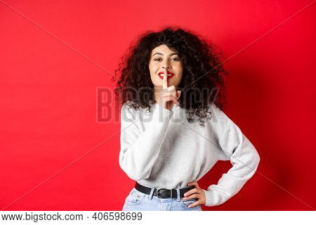 Beautiful Modern Woman With Curly Hair And Makeup, Shushing And Smiling, Telling A Secret, Making Su