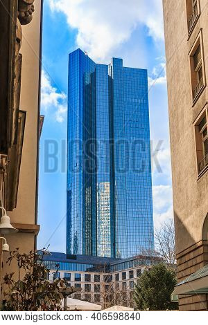 Skyscraper With Glass Facade In Frankfurt In Sunshine With Blue Sky And Clouds. View Between Two Sky