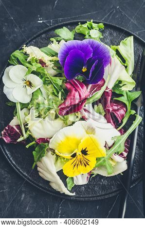 Healthy Salad With Green And Purple Lettuce And Edible Flowers On Black Background. Spring Salad Mix