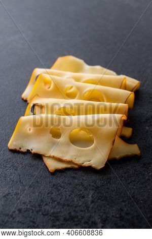 Sliced smoked hard cheese on black table.