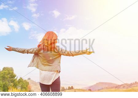 Beautiful Woman Outdoors Enjoying Nature. Fresh Morning Air Of A Summer Field At Dawn. A Red-haired