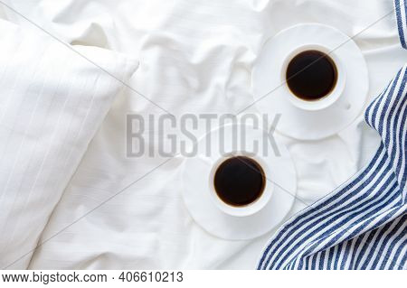 Two Cups Of Coffee On The Bed With White Linens And Blue Bedspread . Good Morning Concept.