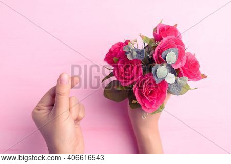 Hand Showing Mini Heart Shape And Holding Red Rose Flower Bouquet On Pink Background, Valentine Day