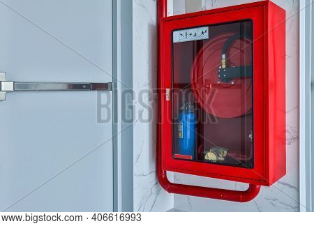 Hydrant With Water Hoses And Fire Extinguish Equipment. Fire Safety Equipment In The Red Box On Wall