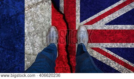 Business Man Stands On Cracked Flag Of Uk And France. Political Concept