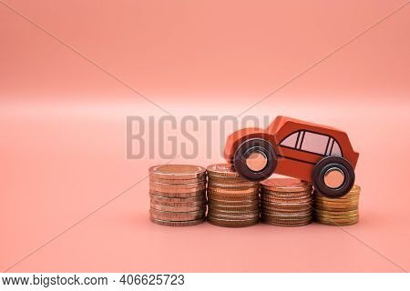 Red Toy Car On Pile Money Stack Coins Growth On Pink Background. Miniature Automobile Model And Busi