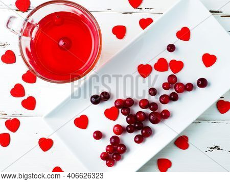 Selective Focus On Cranberries And Red Hearts On A White Rectangular Plate On A White Wooden Backgro