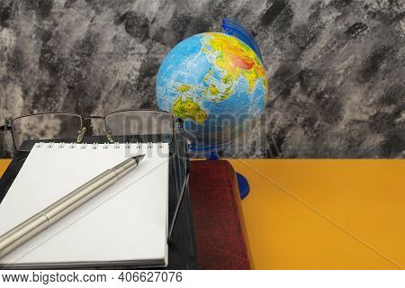 A Large Encyclopedia Book And A Notebook With A Pen Lie On The Desk. Items Book And Glasses, Globe A
