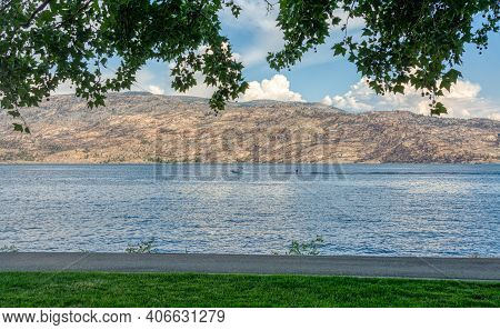 Overview Of Okanagan Lake With A Boat And Waterskiing Man On The Water