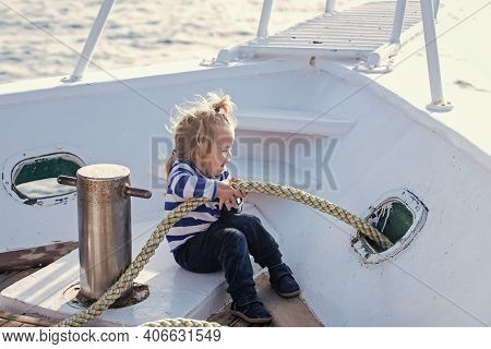 Child Baby Playing With Rope On Yacht. Little Child Sitting And Berthing Rope On White Boat. Travel