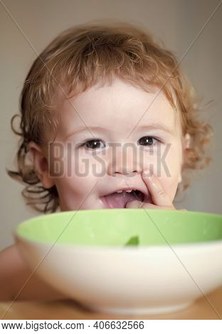 Baby Eating, Cute Child Eat. Portrait Of Smiling Sweet Kid Eating From Plate With Hand