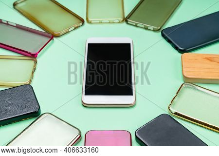 Choice Of Multicolored Plastic Back Covers For Mobile Phones On Green Background With A Smart Phone