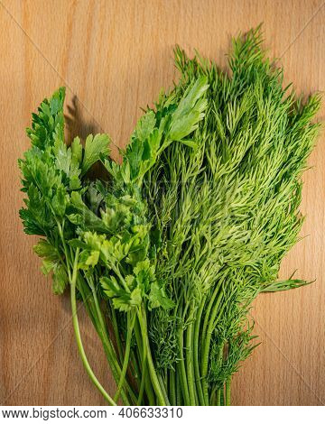 Parsley And Dill Plants Lie On A Wooden Cutting Board. Food Ingredients.