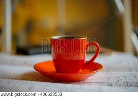 Cup With Coffee On A Plate In The Workroom Stands On The Drawings. Business Concept.