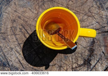 Yellow Cup With A Spoon Full Of Tea Stands On A Cracked Hemp Outdoors. Hot Drinks.