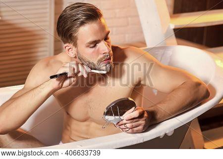 Man Hygiene, Health. Grooming Man Shave With Razor Look At Mirror In Bathtub