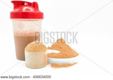 Whey Protein Powder On White Background. Plastic Measuring Dietary Spoon And Bottle Shake Of Chocola