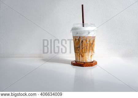 Iced Caramel Macchiato Coffee In A Plastic Cup On A Wooden Table At The Cafe. Cold Espresso In The C