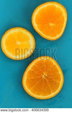 Close Up Of Three Round Orange Citrus Slices On Blue Background, Fresh Summer Mood. Stock Photo Blan