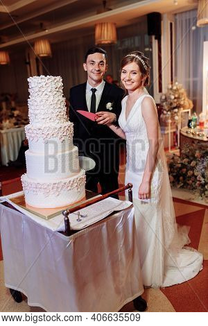 Bride And Groom Holding Hands Cut A Huge Wedding Cake. White Five-layer Wedding Cake. Completion Of